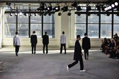 Models posing on the runway wearing Duckie Brown Stock Image
