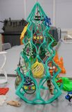 Bright colorful objects printed on a 3d printer on a white table in nano laboratory. New year tree stock photos
