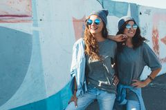 Models wearing plain tshirt and sunglasses posing over street wa. Two models wearing plain gray t-shirts and hipster sunglasses posing against street wall. Teen Stock Photography