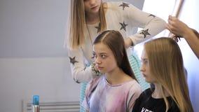 In modelschool wacht de vrouw haar die haar in kapsel wordt gedaan stock video