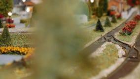 Modeltrein die achter een boom op diorama overgaan stock footage