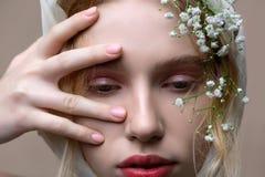 Modeluje z ma?ymi bia?ymi kwiatami w jej w?osy pozuje profesjonalnie obraz royalty free