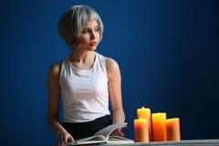 Modeluje z srebnym włosy leafing przez książki z bliska niebieska tła Zdjęcie Royalty Free