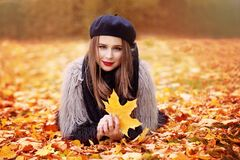 Modelwoman lying op Autumn Leaves Outdoors stock foto