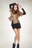 Modemädchen, das in einer Pelzweste und -kurzen Hosen aufwirft Lizenzfreies Stockfoto