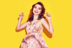 Modemädchen im Kleid auf gelbem Hintergrundtanzen Hübsches Mädchen mit dem lang cerly fliegenden Haar und Rosa bilden Mädchen mit stockbilder
