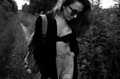 Modemädchen im schwarzen Mantel zieht entlang Waldweg um Lizenzfreies Stockfoto