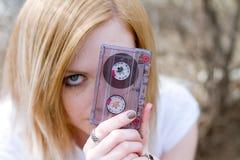 Modemädchen mit einer Kassette in der Hand Stockfotografie