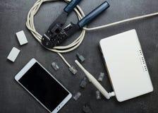 Modem, kontaktdon för vridna par, en crimper och smartphone på grå färger Arkivfoton