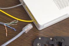 Modem, netwerkkabel en crimper voor het plooien van spaanders, voorzien van een netwerk stock afbeelding