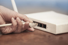 Modem using. Human hand pluging patchcord to the wireless modem Royalty Free Stock Images