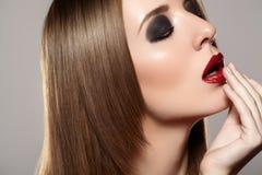 Modemake-up u. -kosmetik. Schönes Baumuster mit den roten Lippen, gerades Haar Lizenzfreie Stockfotografie