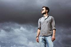 Modeman som poserar på himmelbacdropen royaltyfria foton