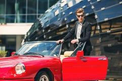 Modeman som står nära den retro cabrioletbilen Royaltyfri Foto