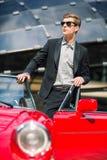 Modeman som står nära den retro cabrioletbilen Arkivbild