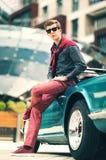 Modeman som står nära den retro cabrioletbilen Arkivfoto