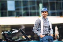 Modemann, der nahe Retro- Cabrioletauto steht Stockbild