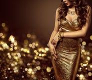 Modemodell Body i den guld- klänningen, elegant guld- kappa för kvinna arkivbild
