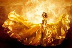 Modemodell Gold Color Skin, fantasikvinnaskönhet i den konstnärliga vinkande klänningen som flyger den siden- kappan fotografering för bildbyråer