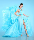 Modemodell i blått som blåser chiffongklänningen Glamour som bedövar Wo royaltyfri fotografi