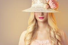 Modemodell i den breda brättehatten med pionblommor, Retro kvinna royaltyfri bild