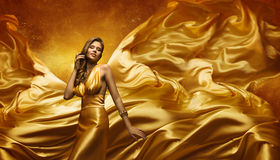 Modemodell i den guld- klänningen, skönhetkvinna som poserar flygtorkduken Arkivfoton
