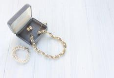Modemodell Jewelry Tappningsmyckenbakgrund Härlig guld- och pärlahalsband, armband och örhängen i en gåvaask på vitt trä Arkivfoton