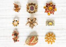Modemodell Jewelry Tappningsmyckenbakgrund Härlig ljus bergkristallbrosch och örhängen på vitt trä Lekmanna- lägenhet, bästa sikt Royaltyfri Fotografi