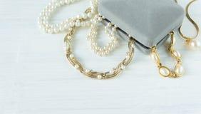 Modemodell Jewelry Tappningsmyckenbakgrund Härliga guld- och pärlemorfärg halsband, armband och örhängen i en gåvaask på vit wo Arkivfoton