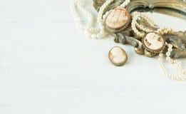Modemodell Jewelry Tappningsmyckenbakgrund Härliga pärlemorfärg halsband-, armband- och kamébroochs på en gammal spegelram plan l Royaltyfria Foton