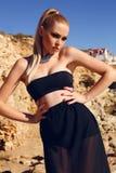 Modemodell med blont hår i den eleganta klänningen som poserar på stranden royaltyfri fotografi