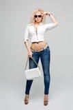 Modemodell med lång bärande solglasögon för lockigt hår som poserar i studio Jeans läderomslag Makeup fylliga kanter På royaltyfri foto