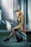 Modemodell med långa sexiga ben som sitter på att tänka för bänk Royaltyfria Bilder