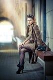 Modemodell med långa sexiga ben som sitter på bänk Fotografering för Bildbyråer
