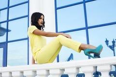 Modemodell med svart hår i elegant gul dräkt fotografering för bildbyråer