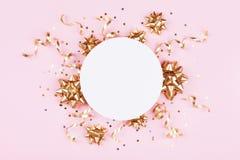 Modemodell mit goldenen Bogen-, Serpentin- und Sternkonfettis auf rosa Pastelltischplatteansicht Flache Lage für Geburtstag oder  lizenzfreies stockfoto