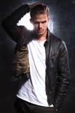 Modemodell som flyttar hans hand till och med hans långa hår arkivfoton