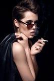 Modemodell som röker bärande solglasögon för cigarett Sexig kvinnastående över mörk bakgrund Attraktivt posera för modeflicka Royaltyfria Bilder