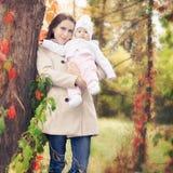 Modemodern som går med henne, behandla som ett barn utomhus- på hösten parkerar Royaltyfri Bild