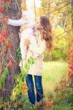 Modemodern som går med henne, behandla som ett barn utomhus- på hösten parkerar Arkivbild