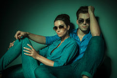 Modepaare, die auf Studiohintergrund sitzen Stockfotografie