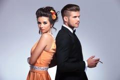 Modepaare zurück zu dem Rückseiten- und Mannrauchen Lizenzfreie Stockbilder
