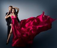 Modepar, ung härlig kvinna, i att flyga den vinkande skönhetklänningen, elegant man royaltyfri fotografi