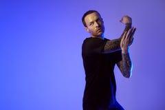 Modeporträt des attraktiven Mannes des Sportsitzes, der Arm herstellt auszudehnen Männlicher nackter Torso, tätowierte Hände, Hip stockbilder