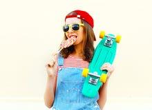 Modeporträt des recht kühlen Mädchens ist Bisse Griffe, die eines Lutschers über Weiß Skateboard fahren Lizenzfreie Stockfotografie