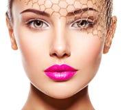 Modeporträt eines schönen Mädchens trägt goldenen Schleier auf Gesicht Stockfoto