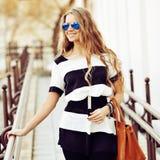 Modeporträt von lächelnden jungen Blondinen mit Handtaschenabnutzung Stockfoto