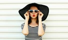 Modeporträtfrau, welche die roten Lippen senden süßen Luftkuß im schwarzen Sommerstrohhut auf weißer Wand durchbrennt lizenzfreie stockbilder