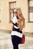 Modeporträt von lächelnden jungen Blondinen mit Handtaschenabnutzung Stockbild