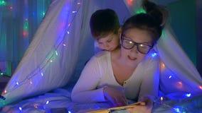 Moder-barnet förhållandet, mum i exponeringsglas läser till litet barnboken för läggdags som ligger i tält med hemmastadda livlig lager videofilmer